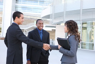 three people in a business shaking hands