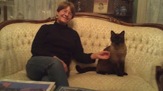 Picture of Margi Erickson and her cat, Simon sitting on a couch in the Parlor