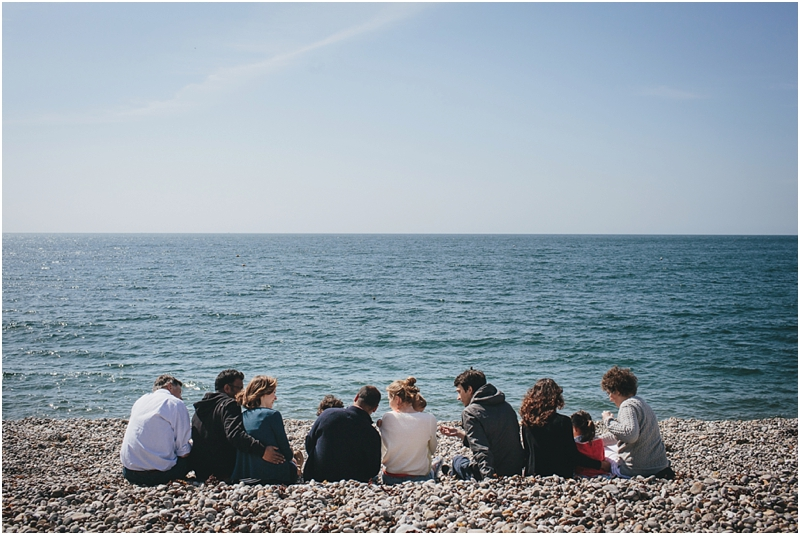 An extended family group sitting by the sea
