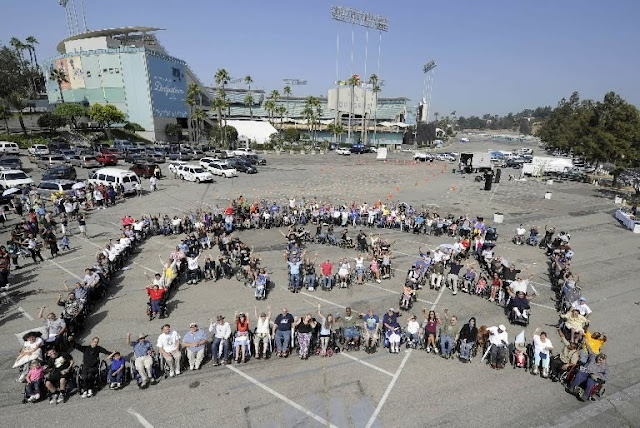 [In a large parking lot, people use their bodies to spell out ADA. Most people appear to use wheelchairs.]