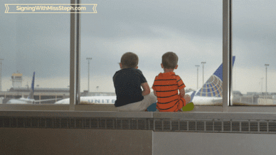 Backs of boys watching planes take off through giant window