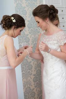 bride has her bridesmaid to help put on her wedding jewellery
