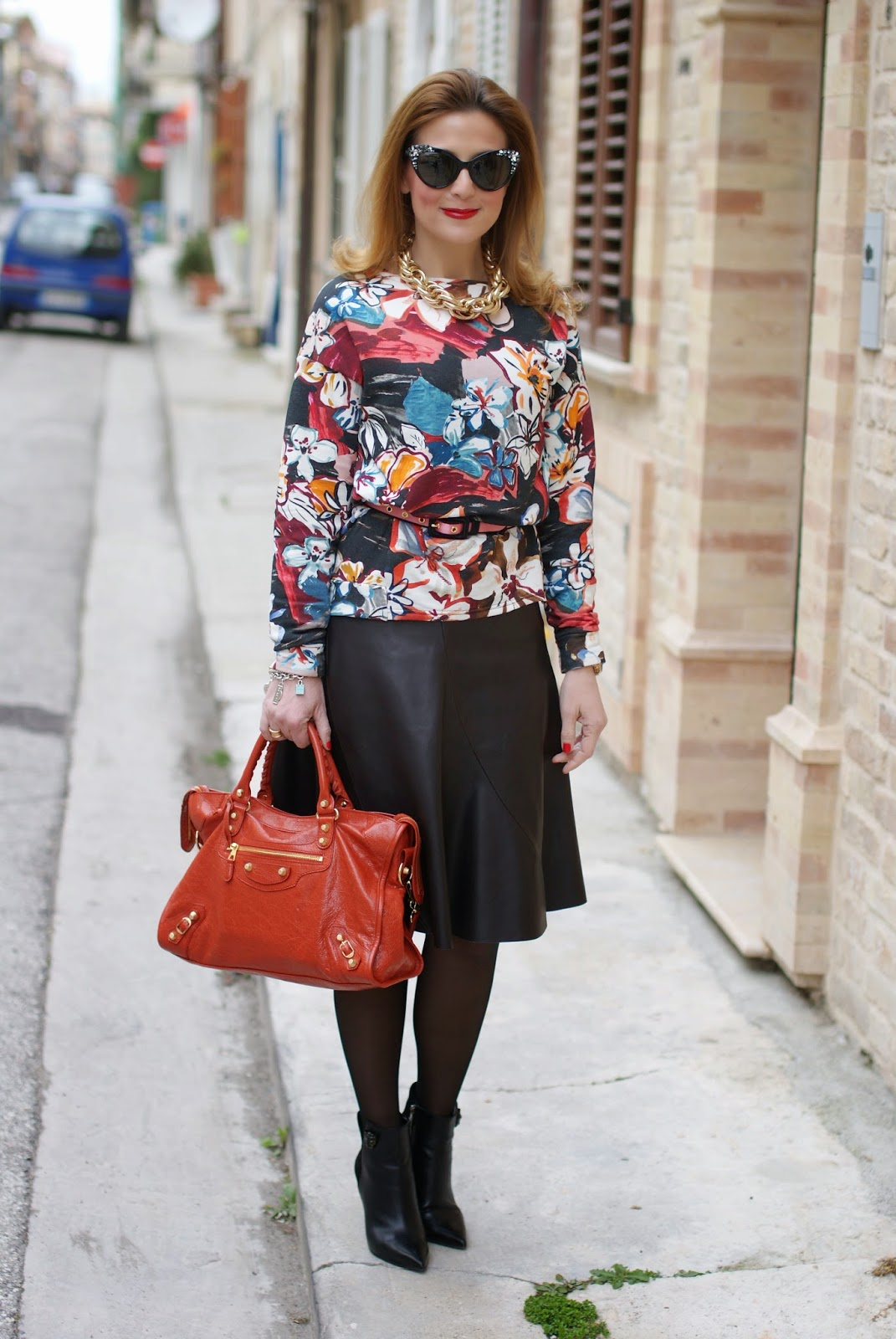 Dsquared2 Crystal cat eye sunglasses found on Giarre.com worn with floral sweatsirt and Balenciaga City bag in rouge ambre, leather skirt and sheer black tights on Fashion and Cookies fashion blog