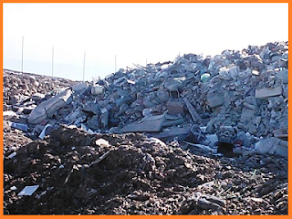 Gray mass of unplowed trash at the landfill surrounded by brown, plowed mass.