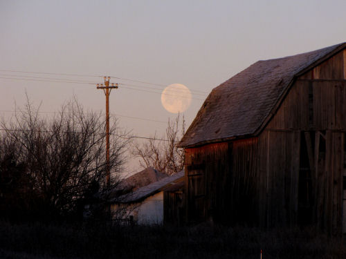 full moon setting over barn