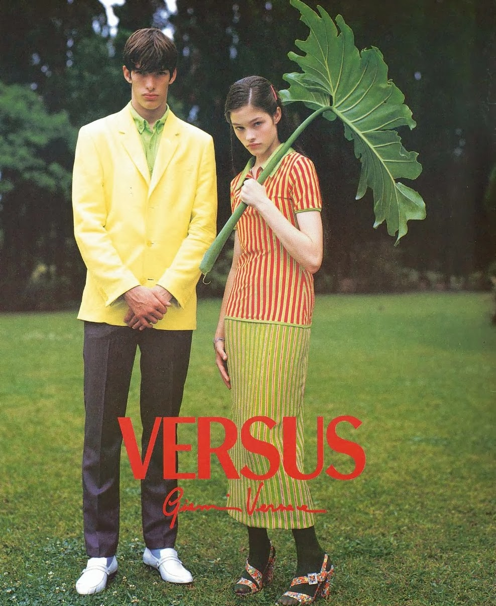 Ivan de Pineda and Lonneke Engel by Bruce Weber, VERSUS s/s 1996, 90's print ad, green grass, boy and girl, big leaf-umbrella, orange, green, springtime, dark stockings and floral heeled sandals with buckles, noncholance, ellow suit-jacket