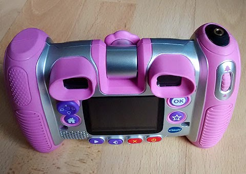 Kiddizoom Twist Plus, switch adapted for use with accessibility switch. (Pink camera and yellow switch). Overhead tilted view including the switch socket on the top of the right-side grip.