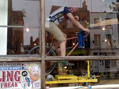 James Bowthorpe cycling in the window of Look Mum No Hands in the Morning