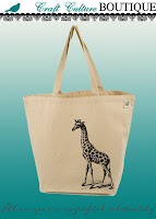 Cream-color canvas tote with long handles. Standing in the lower right corner and stretching up and to the middle of the bag is a realistic-looking drawing of a giraffe. There's shading and shadow on the ground at its feet.