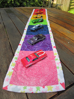 toy cars parked on rainbow coloured quilted table runner