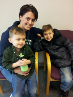 Young woman with pale skin and short, straight dark brown hair, has an arm around each of two young boys, one holding a bottle of milk.