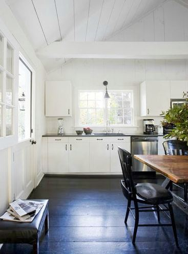kitchen with tongue grove ceiling, dark wood floor, white cabinets and black counter countertops