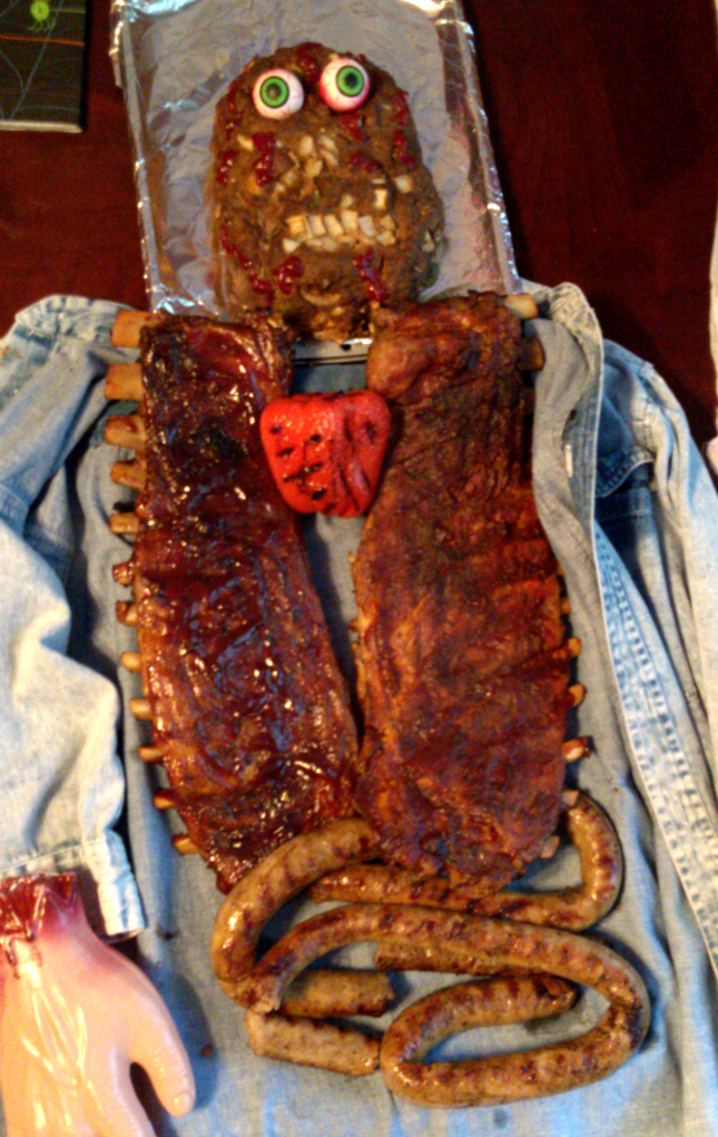 """A Halloween """"corpse"""" made with a meatloaf head, ribs, sausage and a grilled red pepper heart!"""