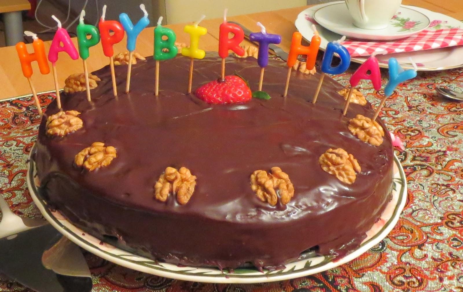Nusstorte mit Schokoladenüberzug, bunten Geburtstagskerzen und Nuss-Dekoration