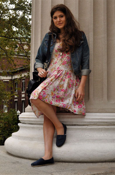 Columbia student wears a pink floral dress, blue toms and a jeans jacket.