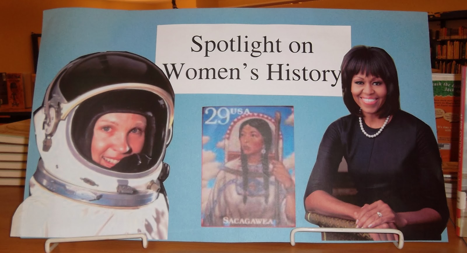 "Blue posterboard with caption ""Spotlight on Women's History."" From left to right, cut-outs attached to the posterboard depict Sally Ride, Sacagawea and Michelle Obama."