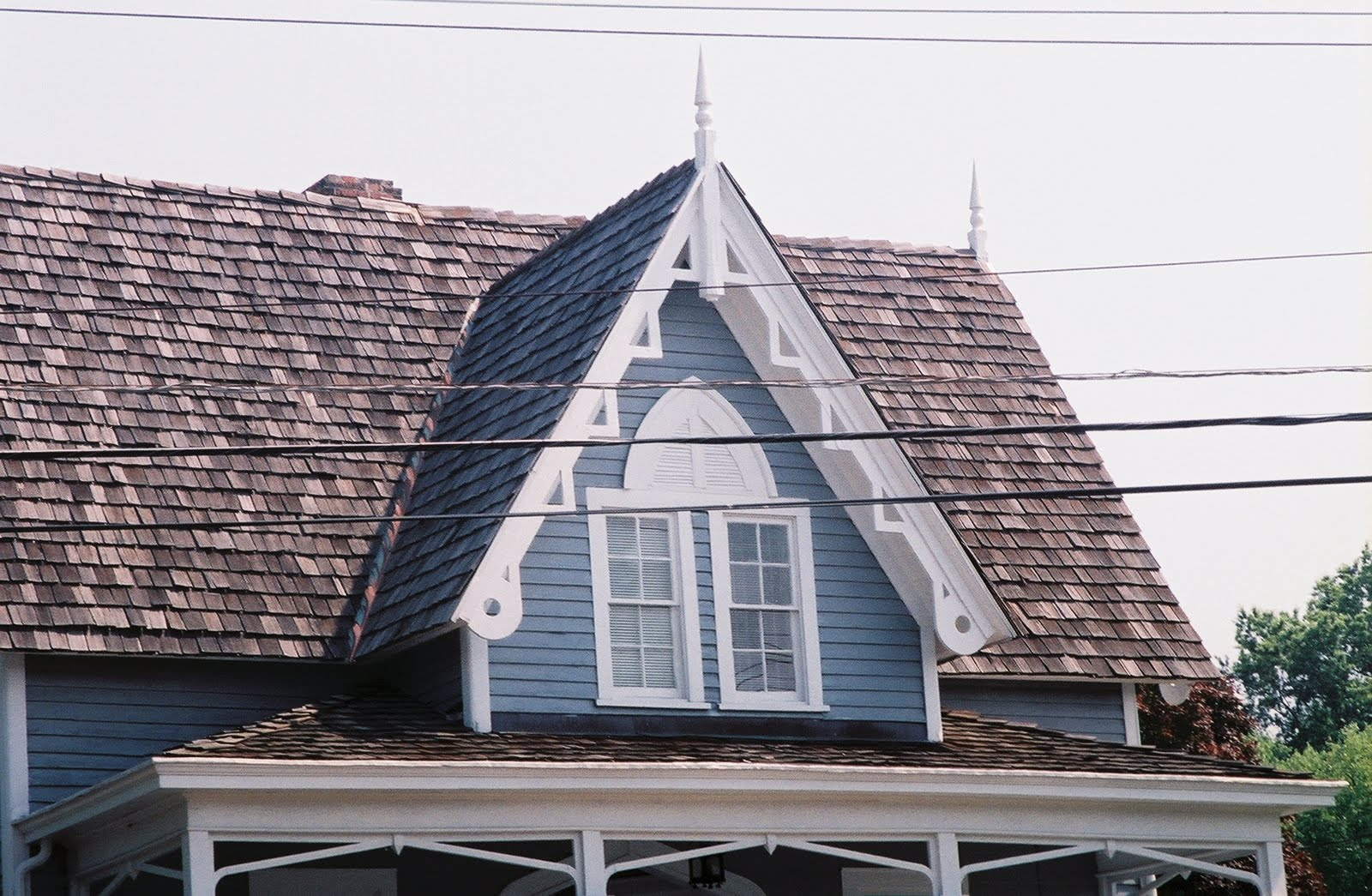 Capped With A Finial Paired Second Floor Four Double Hung Sash Have Decorative Lancet Arched False Shaping Above Windows