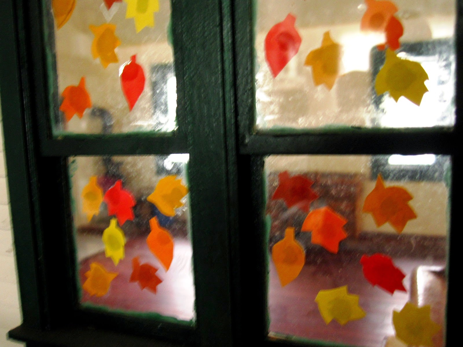 View of an empty vintage miniature school from outside the windows, which have paper autumn leaves stuck on them.