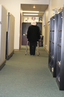 A woman uses her walker in the Stone-Hayes office area