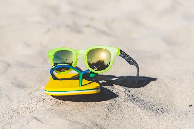Ipanema Sonnenbrille und Sandalen in gelb und grün mit Sonne am Strand