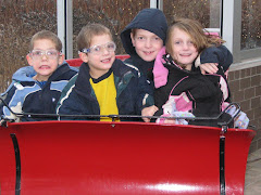 Four kids in a no horse open sleigh