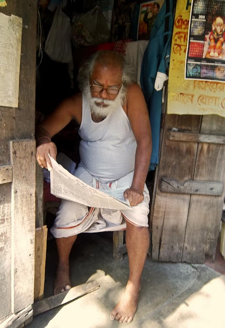 old man reading newspaper in his hut