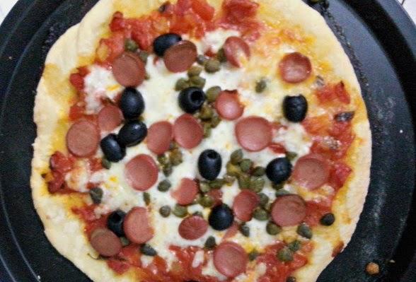 Pizza homemade con wurstel capperi e olive nere