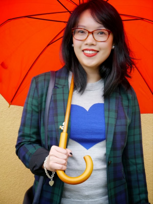 Vancouver blogger Lisa Wong of Solo Lisa wears a plaid JACOB blazer, a grey J. Crew 'Tippi' merino sweater with a blue intarsia heart, and Gap 1969 Always Skinny dark wash jeans. She finishes the look with pearl earrings and a silver bracelet from Maison Birks. To combat the rainy weather, she wears bow-adorned navy blue wellies from Joules and carries a red J. Crew umbrella. Her tortoiseshell framed glasses are by Beausoleil.