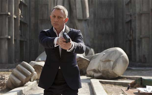 Daniel Craig holding a gun as James Bond in Skyfall movieloversreviews.blogspot.com