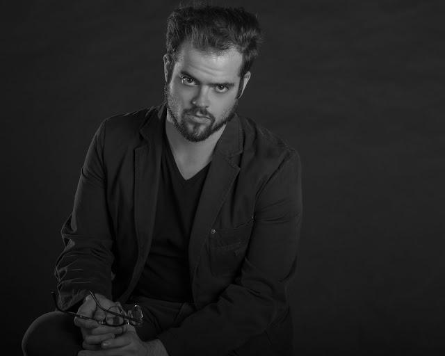 Low-key portrait of writer Brett Caron  sitting on a stool.