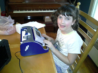 Abby using the smart brailler (its blue she is wearing a white shirt)