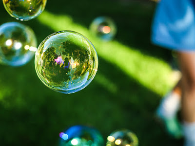 blue-tinged bubbles floating over green grass