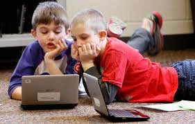 two school age boys laying on the ground with laptops