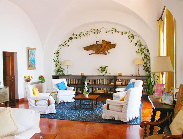 Library in Castiglione castle in Capri with wood floor, white armchairs, arched ceiling and ivy on the wall