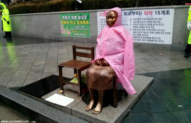 Estatua de una mujer de consuelo coreana con un chubasquero frente a la embajada japonesa