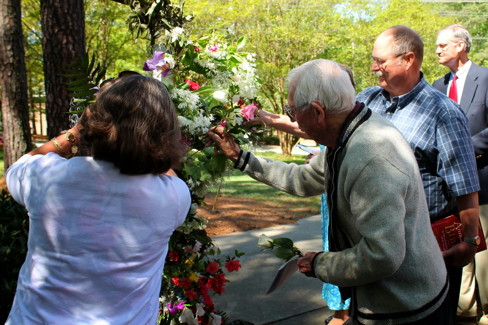 Bob, Bill and friends add flowers to the Easter Cross