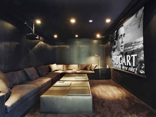 Home theater with projector screen, long sectional sofa and an equally long leather ottoman