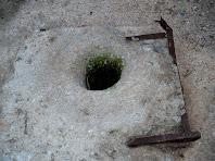 Detall de la boca del pou principal, actualment segellada i transformada en un forat de poc més de quinze centímetres