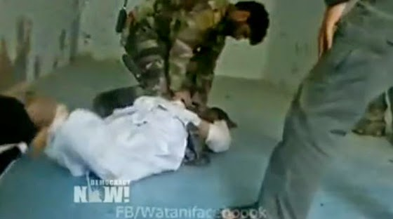 "Afghan soldiers torture a prisoner as ""Western"" soldiers look on. (Screen capture from DemocracyNow)"