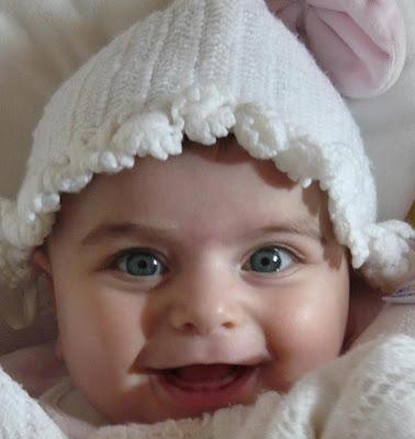 Beyaz Örgü Şapkalı Gülen Bebek