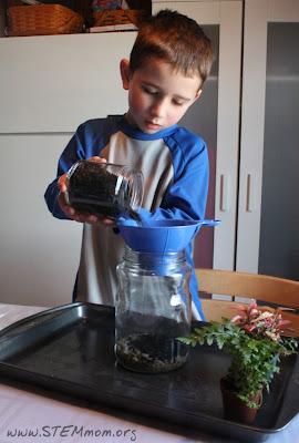 Pouring soil into Terrarium: STEMmom.org
