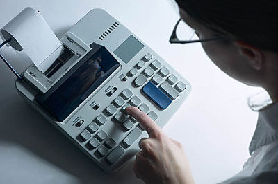 woman using a calculator on desk
