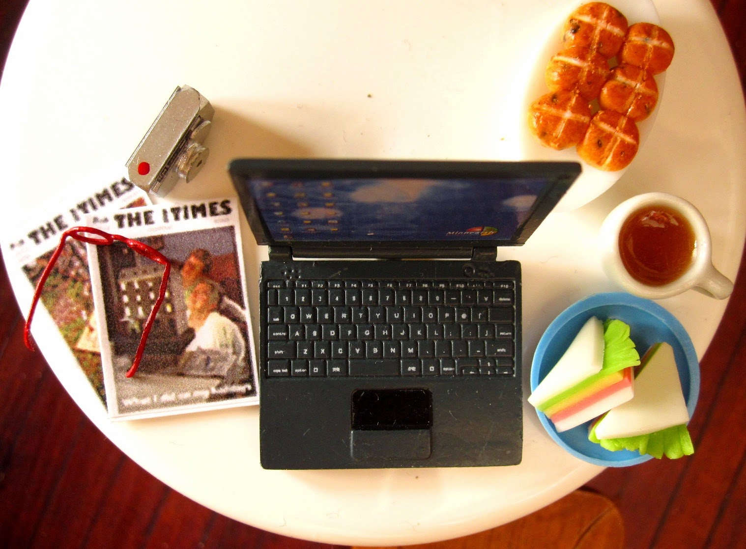 Modern dolls' house miniature round table with a laptop computer, digital camera, reading glasses, back issues of The tiny Times, sandwiches, mug of tea and hot cross buns on it.