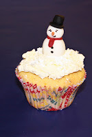 Lemon buttercream cupcake topped with white buttercream snow and a fondant snowman character