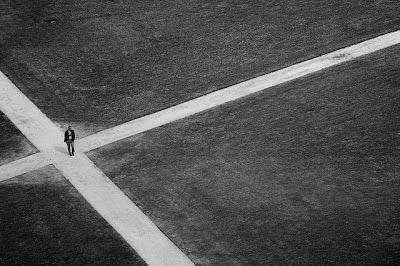 """Cette image montre un homme se trouvant à une intersection, pour être plus précis au point où se recoupent quatre chemins. La composition de l'image est rigoureuse et symétrique, les lignes sont très droites et blanche et complètement vides comme les espaces autour, ce qui accentue l'impression de solitude qui se dégage du spectacle de cet homme qui apparaît également minuscule en vue plongeante. Cette photo très esthétique illustre le poème riche de sens du Marginal Magnifique """"Le dedale"""" dans lequel il est question de choix, de destin et de la difficulté de s'orienter dans la vie. La croisee des chemins symbolisent bien sûr les multiples choix qui nous sont offerts dans la vie, chacun nous entraînant dans une voie différente et sans doute vers un destin différent également. Le Marginal Magnifique insiste sur la difficulté pour l'être humain de savoir ou aller, mais la fin du poeme se veut optimiste et fidèle aux idée du poète qui préconise ouvertement d'éviter les chemins tracés d'avance, qui pour plus sécurisés qu'ils sont offrent bien moins de richesses."""