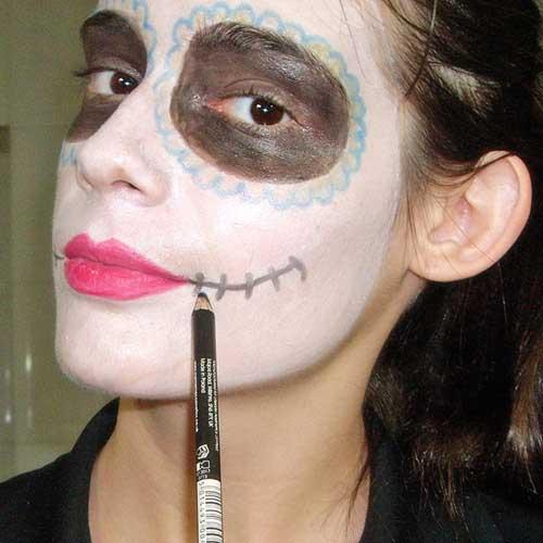 monika sanchez dibujando sonrisa en maquillaje de catrina
