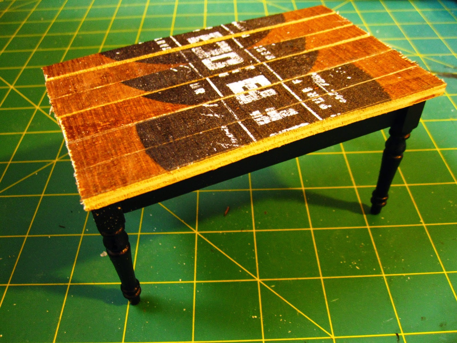 Miniature dining table leg assembly, painted black, topped with a top made of lengths of rustic-looking wood with black printing on them.