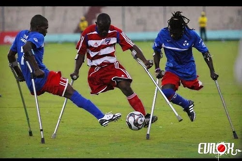 Three young men, all of them one-leg amputees using crutches, playing soccer