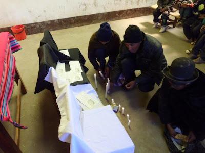 """Gläubige errichten vor dem Altar mit viel Hingabe den mit schwarzen Tüchern versehenen Altar für die """"almas"""" (die Verstorbenen) und zünden Kerzen an."""