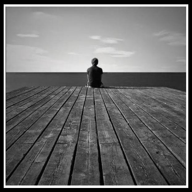 Hombre sentado al final de un muelle, dándonos la espalda. mientras mira el mar, solitario.